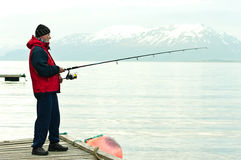 Mens die in fiord vissen Stock Afbeeldingen