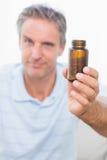 Mens die fles van tabletten tonen aan camera Stock Foto's