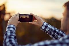 Mens die foto met digitale camera op mobiele telefoon van zonsondergang nemen Royalty-vrije Stock Foto