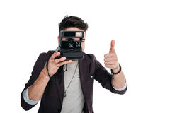 Mens die foto met polaroidcamera nemen en duim tonen Royalty-vrije Stock Foto's