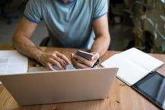 Mens die freelancer aan laptop computer en mobiele telefoon werken, die bij werkstation in bureau zitten Stock Fotografie