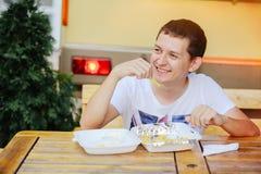 Mens die Frieten en het glimlachen eten Stock Afbeeldingen