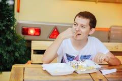 Mens die Frieten en het glimlachen eten Royalty-vrije Stock Foto