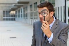 Mens die gebruikend een vergrootglas kijken royalty-vrije stock afbeeldingen