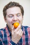 Mens die gehele mandarijn proberen te slikken Royalty-vrije Stock Afbeelding