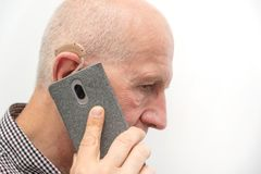 Mens die gehoorapparaat gebruiken terwijl het spreken op de telefoon stock afbeelding