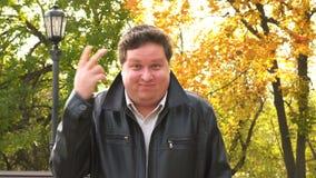 Mens die gek gebaar op de achtergrond van het de herfstpark maken stock videobeelden