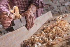 Mens die gekruld houten schroot met het hulpmiddel van het handvliegtuig schaven stock afbeeldingen
