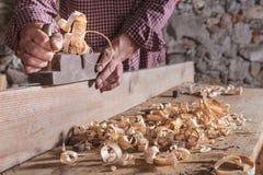 Mens die gekruld houten schroot met het hulpmiddel van het handvliegtuig schaven royalty-vrije stock afbeelding