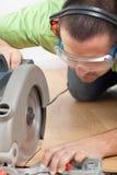 Mens die gelamineerde vloerplank snijden Stock Foto