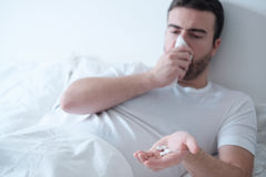 Mens die geneeskundepillen nemen die in het bed liggen Stock Foto