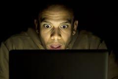 Mens die geschokt zijn laptop laat bij nacht bekijken Royalty-vrije Stock Fotografie