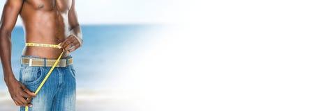 Mens die gewicht met het meten van band op taille op de Zomerstrand meten met overgang stock afbeeldingen