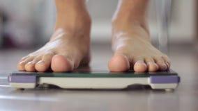 Mens die gewicht op gezondheidsschaal meten stock footage