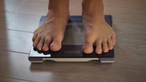 Mens die gewicht op gezondheidsschaal meten stock videobeelden