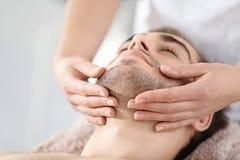 Mens die gezichtsmassage in salon hebben Stock Foto