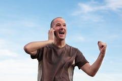 Mens die goed nieuws op de telefoon ontvangt stock afbeelding