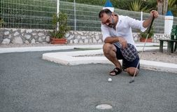 Mens die golfbal met in hand stok bekijken alvorens te werpen royalty-vrije stock foto's