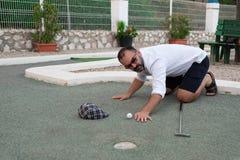 Mens die golfbal met in hand stok bekijken alvorens te werpen royalty-vrije stock afbeelding