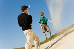 Mens die Golfbal raken uit een Bunker royalty-vrije stock afbeeldingen