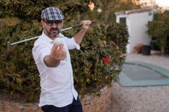 Mens die golfbal in zijn handen met golfclub op zijn rug tonen stock afbeelding