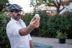 Mens die golfbal in zijn handen tonen royalty-vrije stock afbeelding
