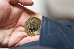 Mens die gouden bitcoin houden hij trekt zich van zijn broekzak terug stock foto