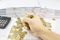 Mens die gouden muntstukken houden Stock Foto