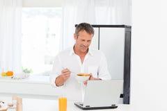 Mens die graangewas eet terwijl hij werkt Stock Fotografie