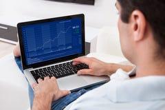 Mens die grafiek op laptop analyseren Stock Foto