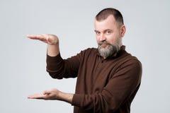 Mens die grote grootte met beide handen tonen royalty-vrije stock foto