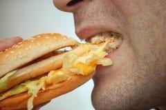 Mens die hamburge eet Royalty-vrije Stock Foto's