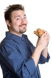 Mens die Hamburger eet Stock Afbeeldingen