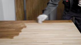 Mens die in handschoenen poetsmiddel met hand op houten paneel zetten stock video
