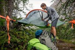 Mens die hangende tent het kamperen klamboe in donkere dag voorbereiden Groep de reis van het de zomeravontuur van vriendenmensen Royalty-vrije Stock Afbeelding