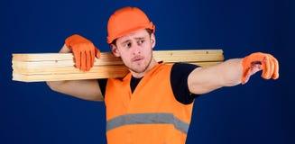 Mens die in helm, bouwvakker en beschermende handschoenen richting, blauwe achtergrond richten Houten materialenconcept timmerman stock foto's