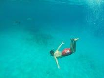 Mens die in het blauwe overzees duikt Stock Foto