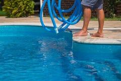 Mens die het blauwe zwembad met slang, close-up schoonmaken Royalty-vrije Stock Afbeeldingen