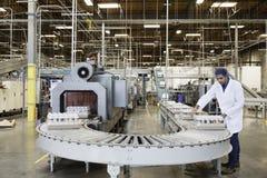 Mens die in het bottelen van fabriek werken stock foto's