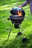 Mens die het deksel van een draagbare barbecuebrand opheffen stock afbeelding