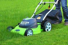 Mens die het gras met grasmaaimachine snijdt royalty-vrije stock foto's