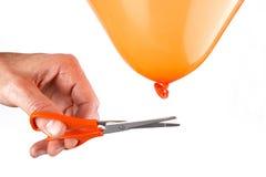 Mens die het koord van een ballon met schaar snijden Stock Fotografie