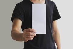 Mens die het lege witte boekje van de vliegerbrochure tonen Pamfletpresentatie De handen van de pamfletgreep De mens toont duidel Stock Fotografie