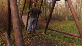 Mens die in het park slingeren stock video