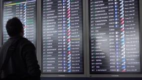 Mens die het programma van vertrek van vliegtuigen bekijken stock video