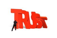 Mens die het rode de domino's van het vertrouwenswoord vallen tegenhouden Royalty-vrije Stock Foto