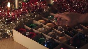 Mens die het rode oude uitstekende stuk speelgoed van het Kerstmisgebied nemen uit de doos stock videobeelden
