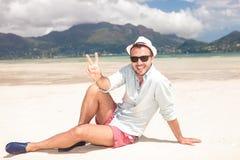 Mens die het teken van de overwinningsvrede op het strand maken Royalty-vrije Stock Foto's