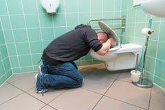 Mens die in het toilet braken stock foto's