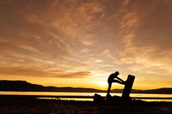 Mens die het uitrekken doen zich bij de zonsondergang Stock Foto's
